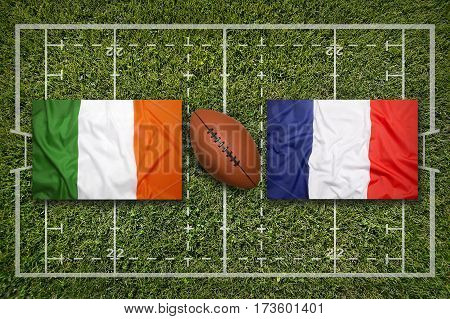 Ireland vs. France flags on green rugby field, 3 D illustration