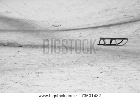 Sledge drag of children isolated on white winter snow with roads in black and white style