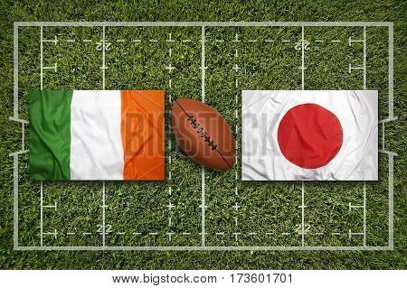 Ireland vs. Japan flags on green rugby field, 3 D illustration
