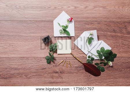 Fountain pen and ink on wooden background. White envelope and red roses. Greeting card. Conceptual photography. Wedding invitation card with pen. Valentine day. Tips to pen. Flat lay pen copyspace mock up