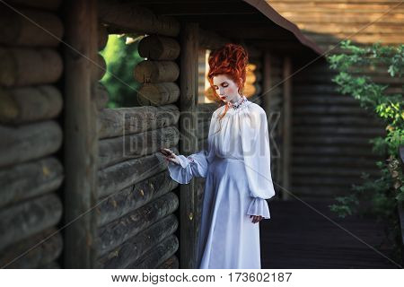 Beautiful redhead renaissance girl with a high hair in an old white dress in the park. The Victorian era. Historic renaissance costume. White Queen. Princess castle