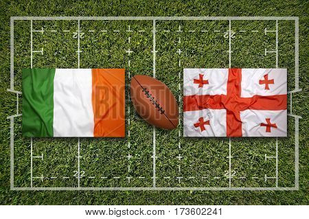 Ireland vs. Georgia flags on green rugby field, 3 D illustration