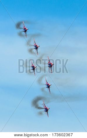 A group of six fighter aircraft in the blue sky with smoke. Russia. Moscow 28 August 2015