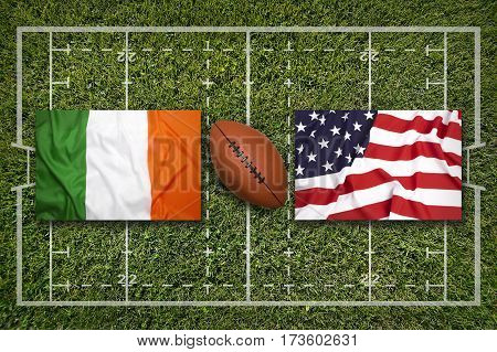 Ireland vs. USA flags on green rugby field, 3 D illustration