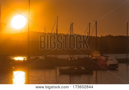 Sailboat silhouettes, magnificent golden warm sunset in Ibiza marina.
