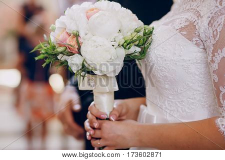 bride standing with flowers in church alone