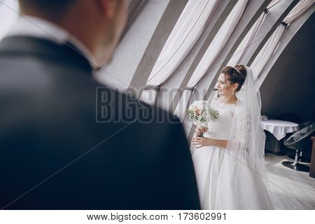 bride in a white dress and the groom standing at the high windows