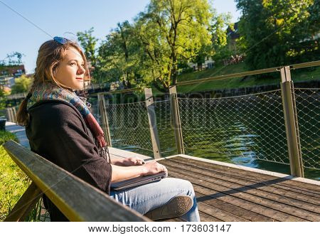 Young and attractive woman meditating with closed laptop. Feeling free.