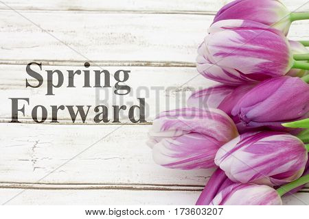 Spring Forward message A bouquet of purple tulips on weathered wood with text Spring Forward