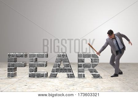 Angry man with baseball bat hitting fear word