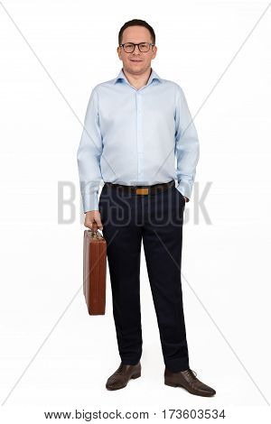 Happy smiling businessman in blue shirt blue pants and glasses posing with brown leather briefcase against white background - business people and office concept