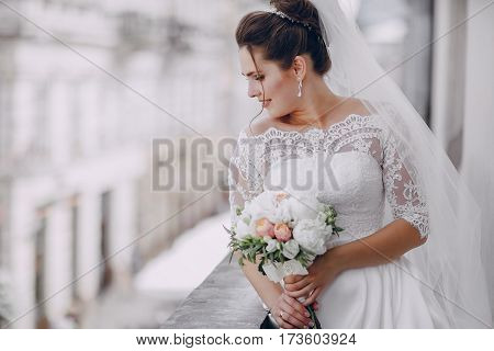 The bride standing on the balcony and holding a bouquet of flowers