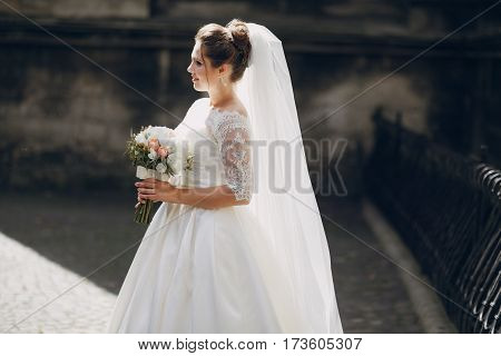 bride standing against a wall and holding a bouquet of peonies