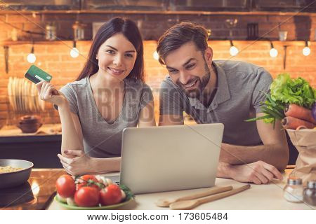 Order food online. Couple in kitchen ordering food online from restaurant. They using laptop. Woman looking at camera and smiling while paying with credit card. Nice loft interior with light bulbs