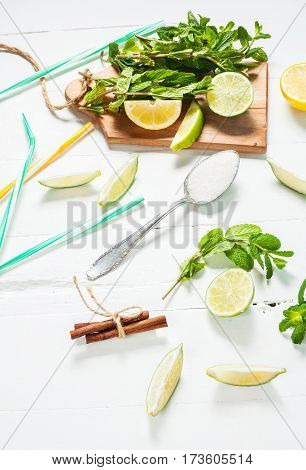 Ingredients for making mojitos - mint leaves sugar and lime on white background