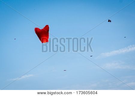 Chinese lantern floats against a blue sky with kites flying against it during the festival of Makar Sankranti in Jaipur India