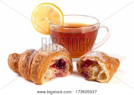 a croissant with a cup of tea isolated on a white background closeup.