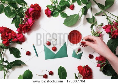 Roses frame. Female hand with red fingernails holding a cup of tea red tea ripe cherries small envelopes roses lay on a white background with roses. Tea drinking during work. Healing drink with roses. Berry compote. Flat lay roses
