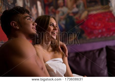Young sexy pair sitting close to each other embracing anf smiling shot in sauna luxurious interior