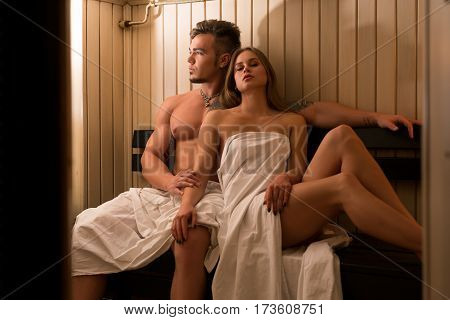 Young sexy pair relaxing shot in sauna steam room