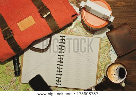 Some travel equipment like vintage backpack wallet food containers cell phone and of course a map