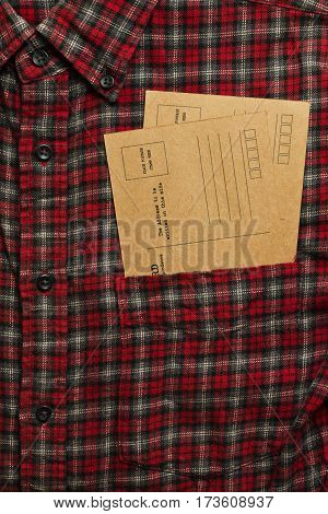Male checkered cowboy's shirt with two vintage postcards in the pocket