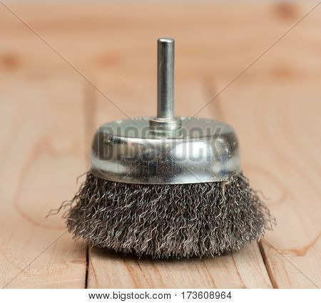 metal brush on a drill to remove rust on a light wooden background.
