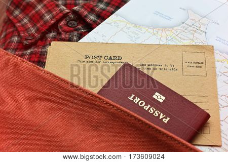 Checkered shirt, map, postcards and passport in retro styled backpack