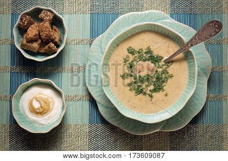 Delicious cream cheese soup with mushrooms served with crackers and mustard sauce