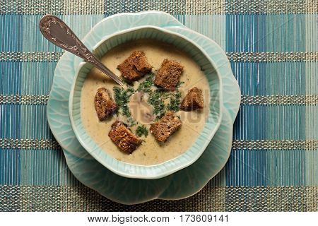 Delicious cream soup with crackers in exotic crockery