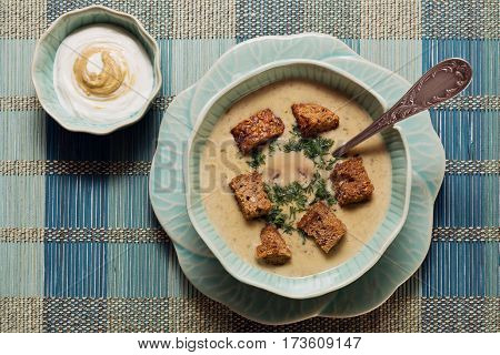Cheese soup with mushrooms and crackers served in aquamarine flower-like crockery
