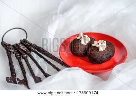 Cakes made of chocolate on a red plate on a white background. Cakes decorated with red jelly and delicate white cream. The metal key.