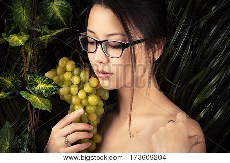 feminine pretty Korean girl in glasses with grapes