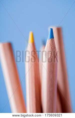 Macro view of crayons. Colored Pencils. Colored pencils on the blue background. Tips of the pencils. Drawing and painting. Artist. Blur.
