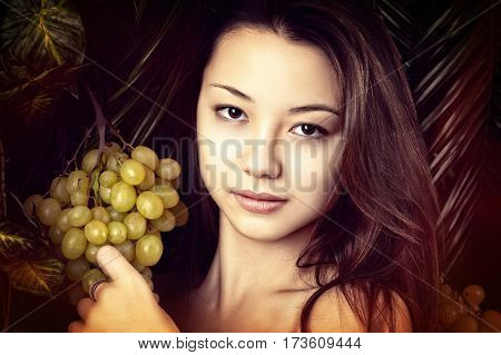 beautiful portrait girl with grapes close up