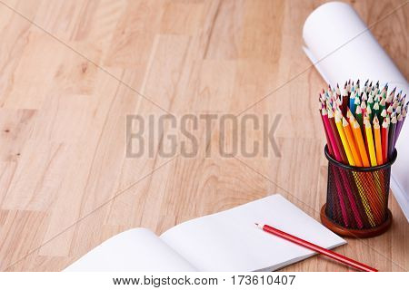 Top view of paper roll and school supplies on the wood background. Pencils and notebook. Brown table. Pencils in the clerical glass. Drawing and painting. School and education.