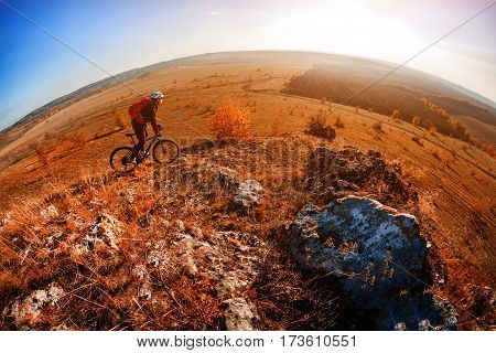 Cyclist riding a bike on an off road to the sunset. Wild landscape. Travel in the countryside. Cyclist with helmet and red backpack. Fisheye.