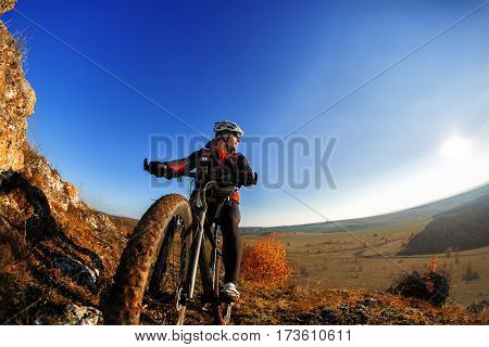 Cyclist Riding the Bike Down Rocky Hill at Sunset. Close up Extreme Sport Concept. Space for Text. Fisheye. Wild angle. Cyclist in the helmet. Background with blue sky. Detail of the cycle. Wheel.