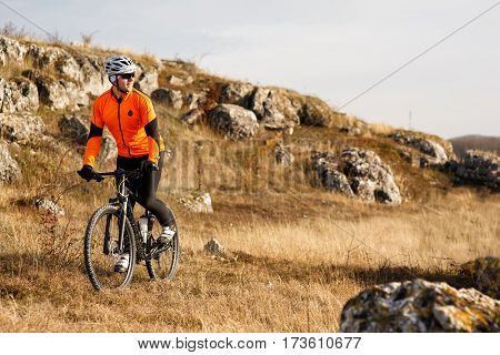 Cyclist in Orange Jacket Riding the Bike on the Rocky Trail. Extreme Sport Concept. Space for Text. MAn in the white helmet and glasses. Travel in the countyrside. Landscape with hill and rocks.