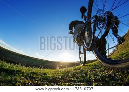 closeup of a cyclist on a sport mountain bike. travel in countryside. Wide angle and fisheye. Detail of the cycle. Wheel. Legs and hand. Blue sky and green grass. Sunset. Sunrise.