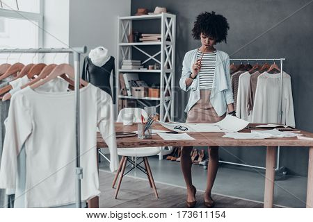 Generating fresh ideas. Full length of young African woman touching lips with pencil and looking at paper while standing in her workshop near the clothes hanging on the racks