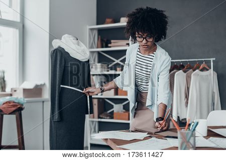 Working on new collection. Concentrated young African woman measuring waist with tape and writing down the results while standing in her workshop with clothes hanging in the background