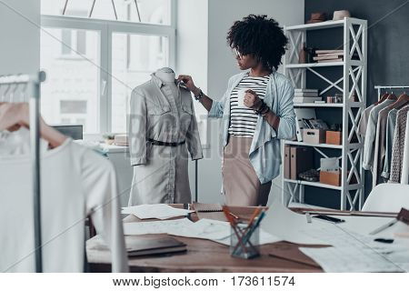 Everything must be perfect. Beautiful young African woman adjusting a collar of the dress on mannequin and holding a cup while standing in her workshop