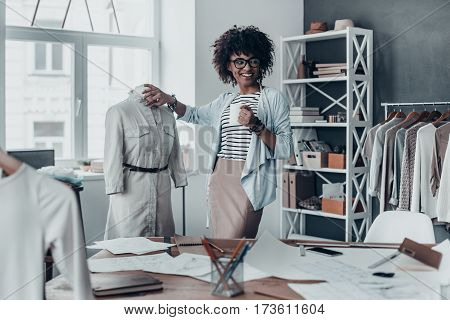 Perfect design. Beautiful young African woman touching mannequin with hand and holding a cup while standing in her workshop