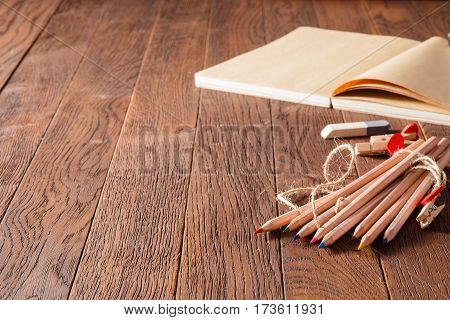 Blank notebook and colorful pencils on the wooden table. Eraser and wooden pins. Brown background. Decorative rope. Natural materials. School. Painting and drawing.