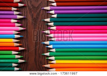 Color Pencils on wood texture. Macro shot of colorful pencils. Horizontal view of pencils. Pencil tips combined opposite each other. Brown background. Creative. School. Education.