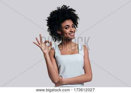 Everything is perfect. Young beautiful African woman in casual wear gesturing and looking at camera while standing against grey background