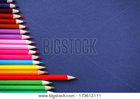 one red pencil standing out from the series of colorful pencils. on blue background. Sign symbol idea concept of leadership, opposition, confrontation. Standoff of the individual to society