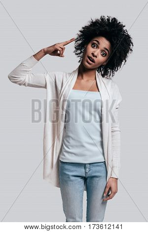 Shocking news. Surprised young African woman with opened mouth pointing on her head and looking at camera while standing against grey background
