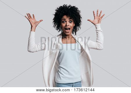 Totally shocked. Surprised young African woman with opened mouth gesturing and looking at camera while standing against grey background